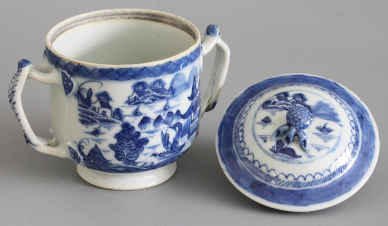 A fine antique Chinese Qianlong style porcelain twin handled lidded blue and white watery landscape painted cup probably dating to the 18th or possibly early 19th century. The cup stands raised on a narrow rounded foot with a cut and unglazed foot