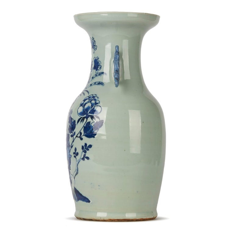A stunning and large antique Chinese Qing twin handled porcelain vase decorated in blue and white with a bird perched on a branch amidst various flowering shrubs the scene painted against a celadon ground. The bulbous shaped vase has stylised dragon