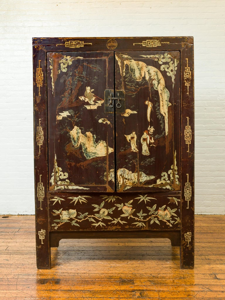 A Chinese Qing dynasty brown lacquered two-door cabinet from the early 20th century, with hand painted chinoiserie décor. Born in China during the early years of the 20th century this cabinet features a brown lacquered finish showing a nicely
