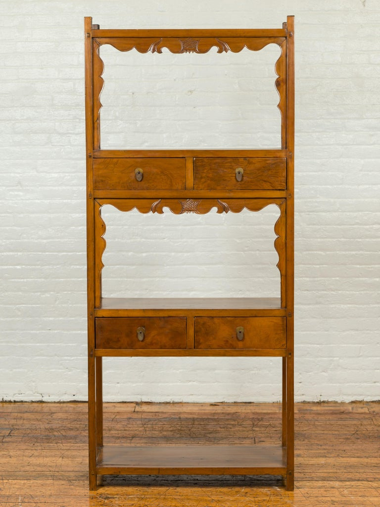A Chinese Qing dynasty elmwood bookcase from the 19th century, with three open shelves and four drawers. Born in China during the Qing dynasty period, this elm bookcase features three open shelving areas, two of which are accented with scrolling