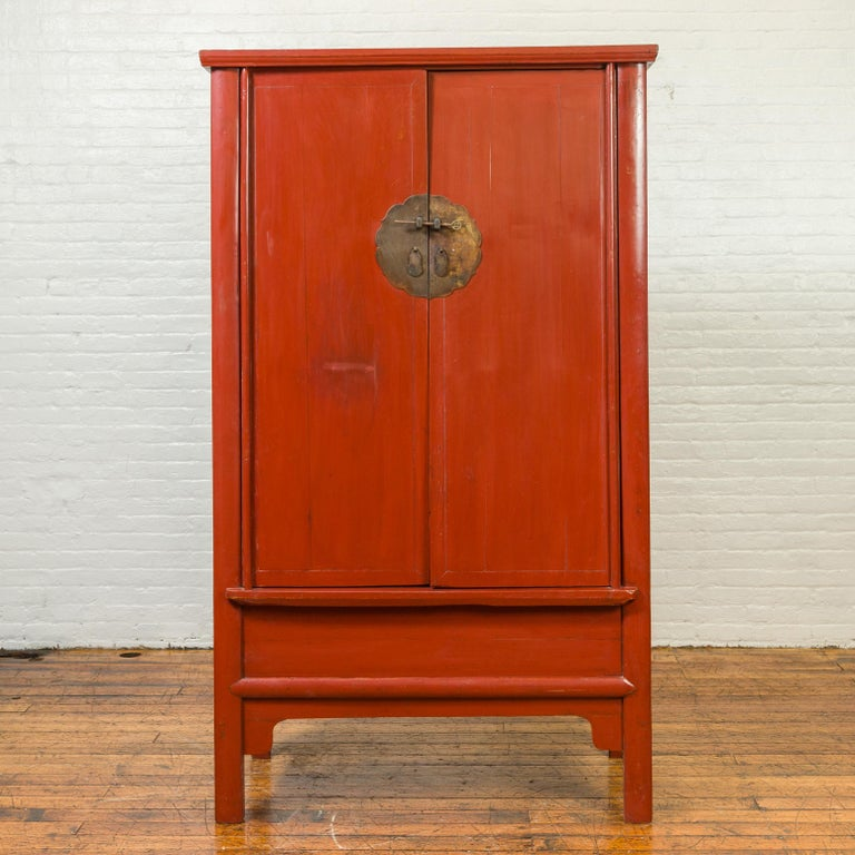 A Chinese Qing Dynasty period red lacquered armoire from the 19th century, with bronze medallion and apron. Created in China during the Qing Dynasty, this red lacquered armoire features two doors, adorned with a large bronze medallion locking thanks