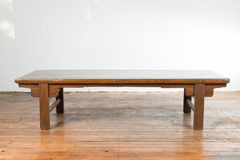 A Chinese Qing Dynasty period wide coffee table from the 19th century, with carved spandrels and side stretchers. Created in China during the Qing Dynasty period, this coffee table features a wide rectangular planked top sitting above four straight