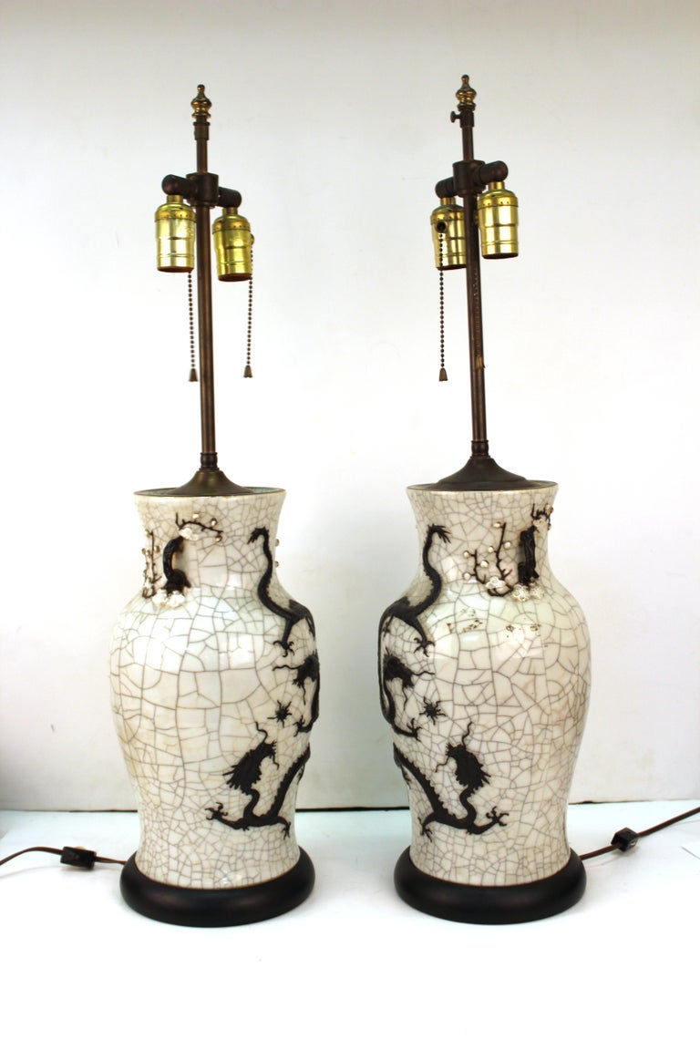 Chinese Qing dynasty pair of vases with crackle glaze and molded dragons. The pair is mounted on circular bases and transformed into table lamps. Made in the circa 1870s, the vases are in great antique condition with age-appropriate wear and use.