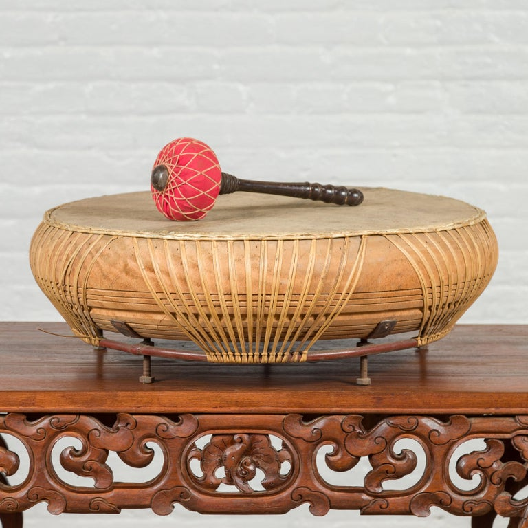 A Chinese Qing dynasty period leather drum from the 19th century, with turned wood red mallet. Created in China during the Qing dynasty, this round leather drum will make for an exquisite decorative accent in any home. Freestanding, it comes with