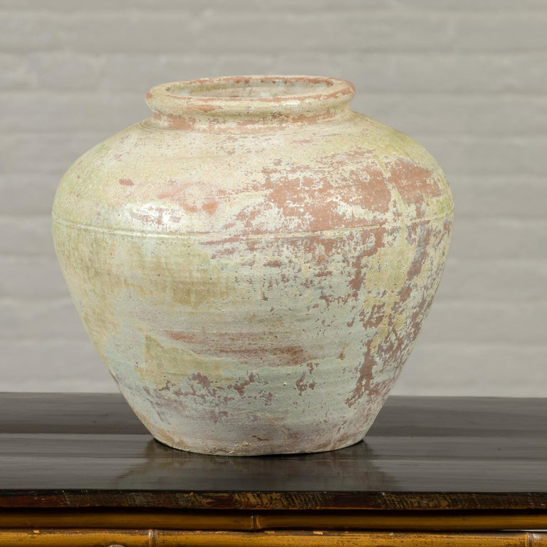 A Chinese Qing Dynasty period exterior vase from the 19th century with light yellow green glaze and weathered appearance. Crafted in China during the Qing Dynasty, this vase will make for an excellent garden ornament. Presenting a nicely weathered