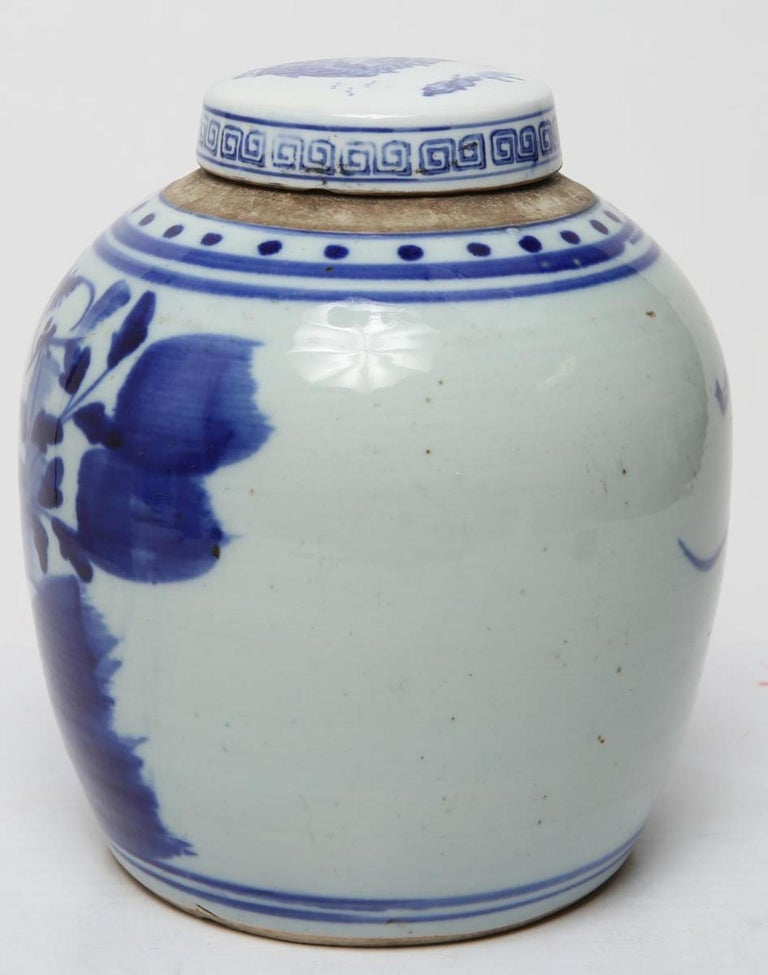 Chinese Qing dynasty ginger jar in underglaze blue and white porcelain, painted with lotus flowers, buds and pods; the lid with tiny landscape and Greek key border. In good vintage condition.