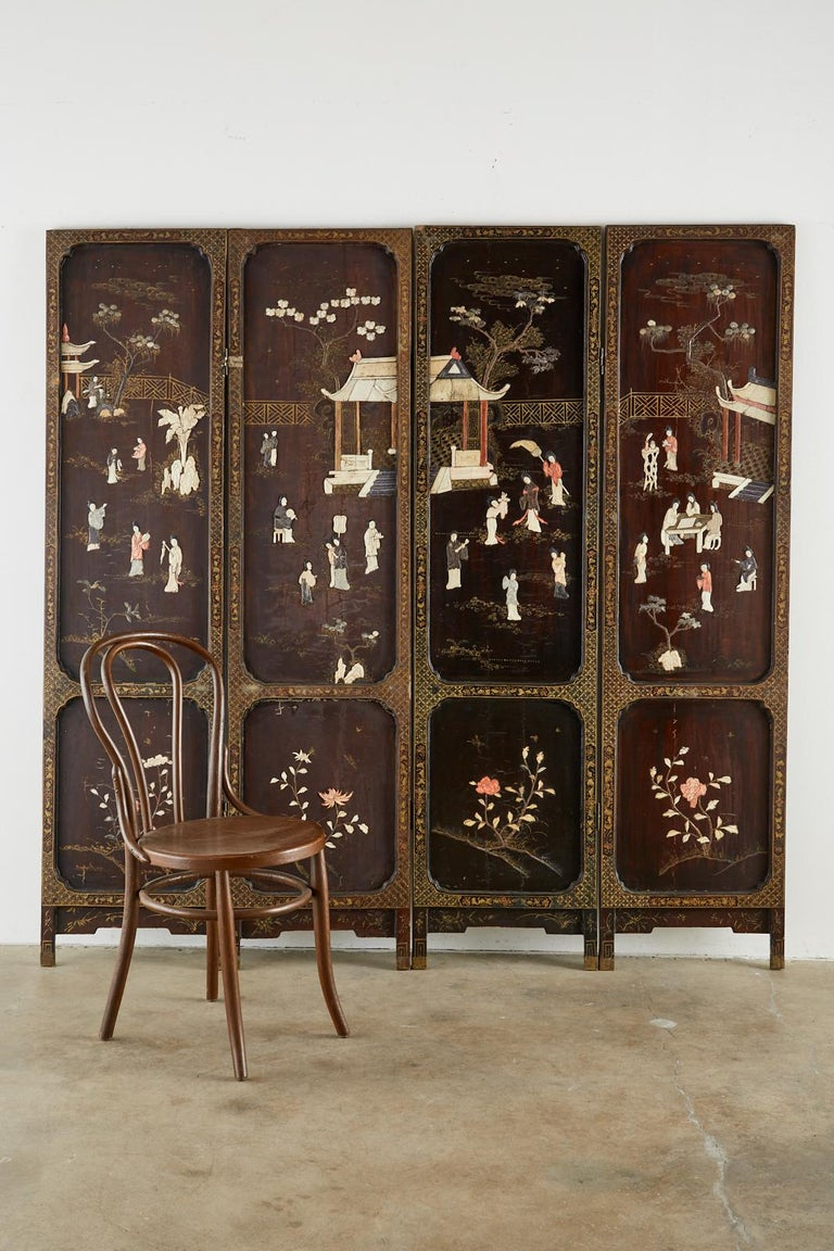 Impressive Chinese late Qing dynasty four panel folding coromandel screen featuring carved soapstone. The lacquered panels are decorated with idyllic scenes of beauties in a pagoda pavilion engaged in leisurely activities. The bottom of each panel