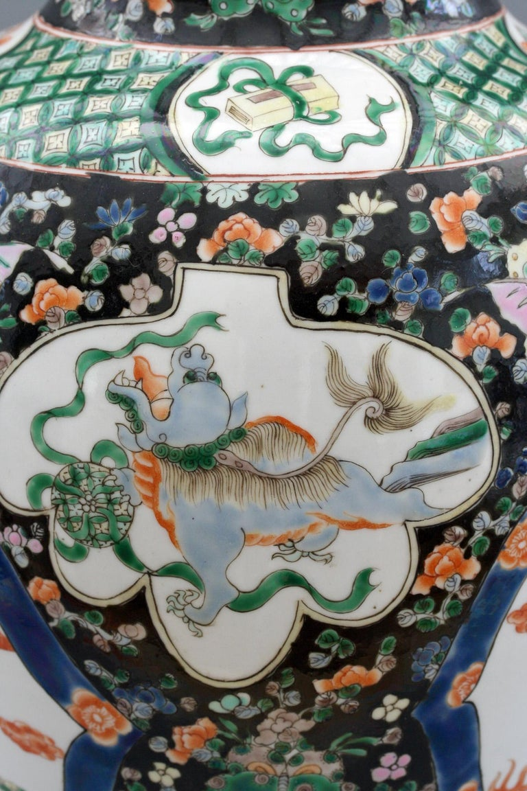 A well decorated antique Chinese Kangxi mark Famille noire porcelain baluster shaped vase dating from the 19th century. This tall and impressive vase is decorated with two large arched panels, one painted with a dragon and phoenix bird and the other
