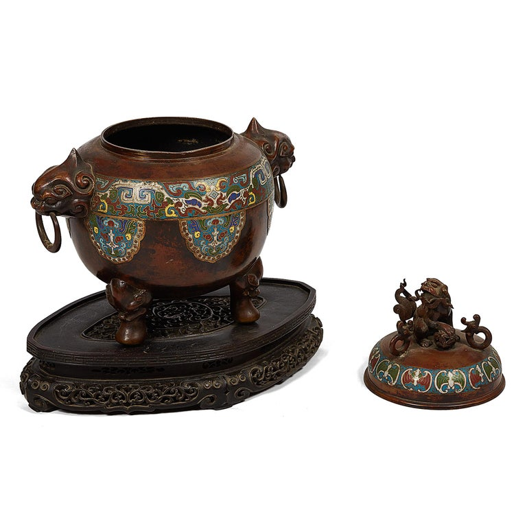 This Japanese censer incense burner, inspired by Chinese pieces, is of spheroidal form, the bronze body with polychrome champlevé enamel work flanked by dragon-head handles and ring pulls. The lid with a decorative polychrome champlevé enameled band