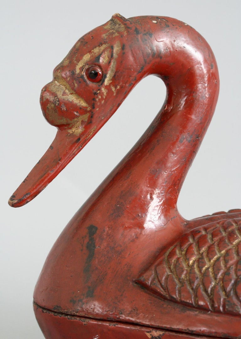 An unusual antique Chinese Qing red lacquered wooden lidded box modeled as a duck dating from the later 19th century. The duck is modeled seated with its legs resting beneath its body which forms the box. The cover is formed of the duck's upper body