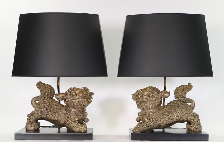 Chinese late Qing dynasty pair of table lamps with silver plated bronze foo dogs or foo dragons, mounted on ebonized wood bases. The sculptures have intricate metal carving and date from the early 20th century. The pair is fully restored with all