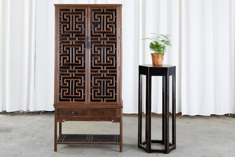 Magnificent Chinese two-piece kitchen cabinet featuring a carved lattice open fretwork cupboard case. Made in the Qing style from beautifully grained hardwood. The kitchen cabinet top has two doors with brass pulls that open to a three shelf storage