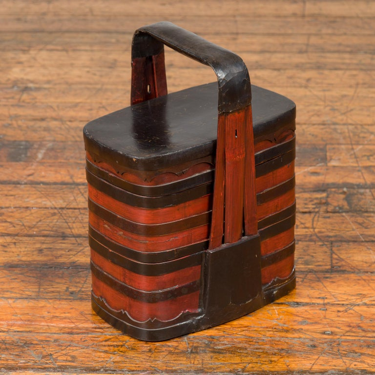 A Chinese antique red and black lacquered tiered lunch box from the early 20th century, with large handle and calligraphy. Crafted in China during the early years of the 20th century, this tiered lunch box features a black lid adorned with painted