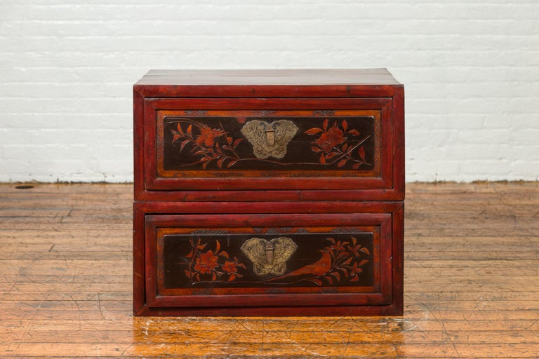 An antique Chinese red and black lacquered two-part storage cabinet with butterfly bronze hardware and carved floral design. Crafted in China, this two-sectioned storage cabinet features a red lacquered body accented with black lacquer on the