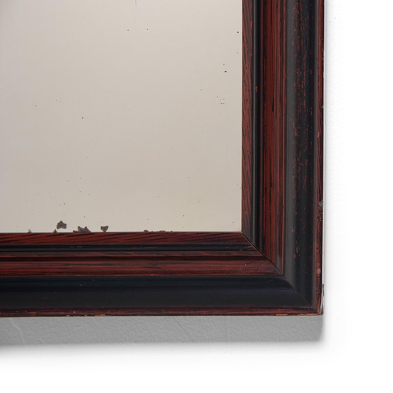 This charming wall mirror was crafted in China's Guangdong province and dates to the early 20th century. The rectangular frame is colored with finely brushed red and black lacquer, for a rustic finish. The mitered frame encloses the original mirror,