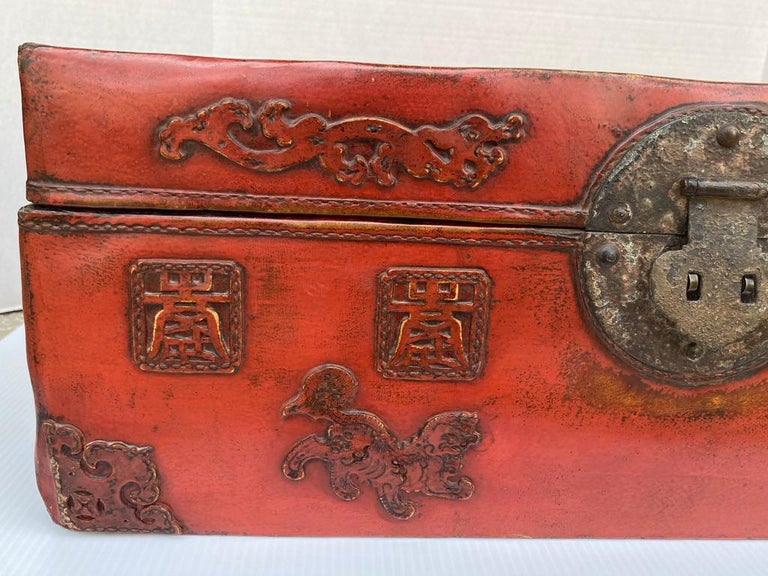 This Chinese leather trunk is red lacquered having