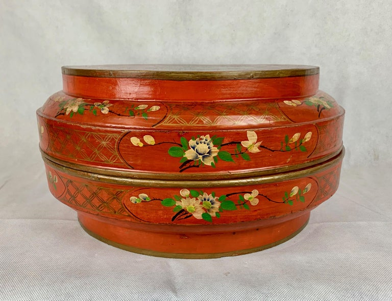 Chinese red lacquer two part wedding box. Entirely hand decorated with a bird and flowers on top and flowers and vines along the side.  The interior is painted a deep apple green. Diameter-15.5