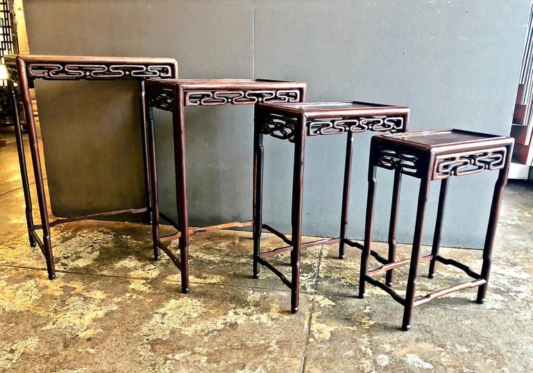 This is a good set of 4 Chinese carved rosewood nesting or quartteto tables that date to the late 19th or early 20th century. The carved wave-form skirts and shaped legs are indications of the quality level and attention to detail given by the