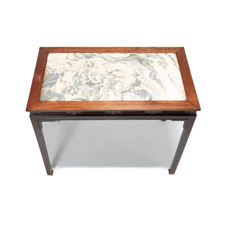 This vintage rosewood side table from Beijing was crafted with graceful proportions in the manner of Ming design. It features a hand carved beaded apron, square legs ending in hoof feet, and a marble top selected for its resemblance to a Chinese