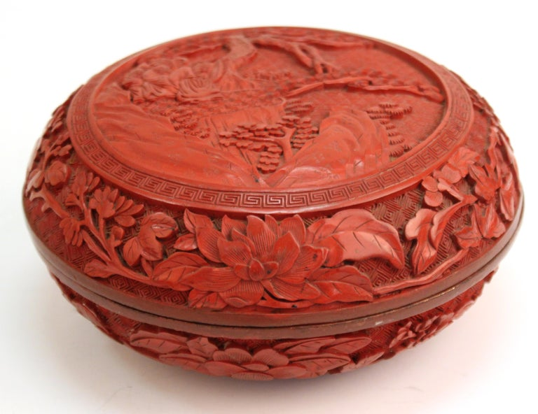 Chinese round Cinnabar box with carved lid depicting a scene of five scholars in a garden. The piece was made in China during the 1930s and is in great vintage condition with age-appropriate wear.