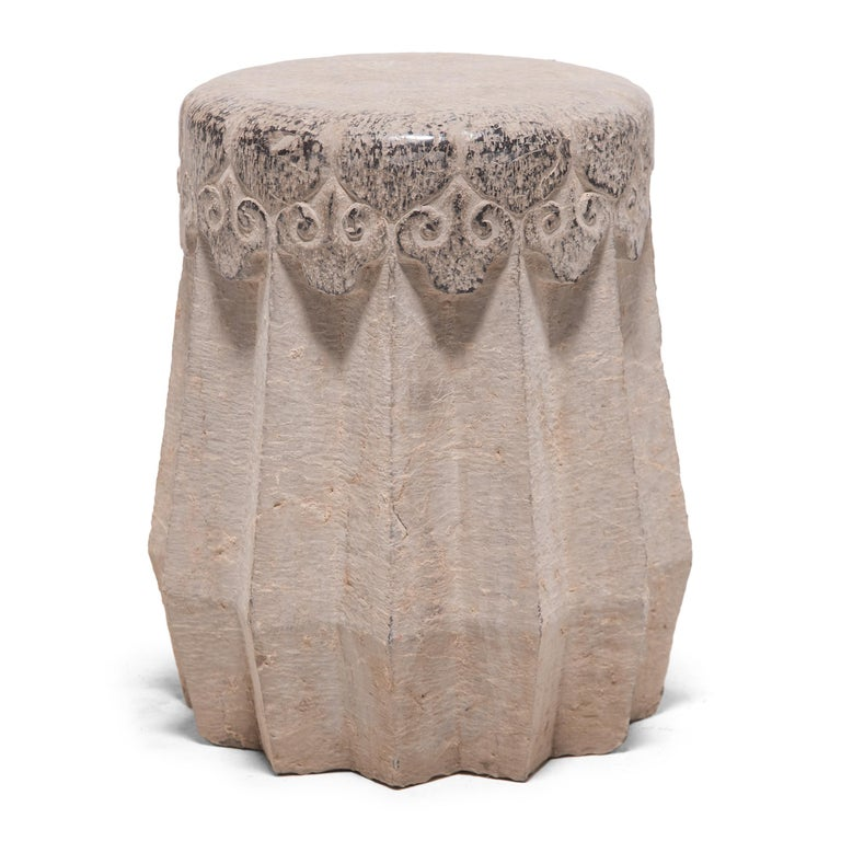 Carved from a solid block of limestone, this early 20th century drum stool began its life in China's Shanxi province. A variation of the traditional melon form, the stool has angular ridges running down the sides in a zig-zag pattern. The smoothed