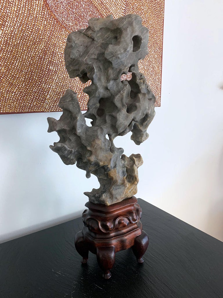An elegant Taihu scholar rock balanced on a custom wood stand, in a mushroom cloud form and full of grottoes. The weather-smoothed surface is of a whitish grey color and is interspersed with white veins and yellow calcification, in a most artistic