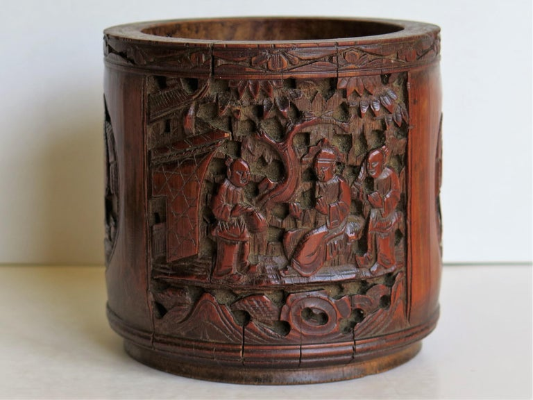 This is a finely hand-carved Chinese bamboo scholars brush pot or bitong which we date to the mid-19th century of the Qing dynasty, circa 1850, but could be earlier.  The bamboo has been intricately hand-carved in four different alternating