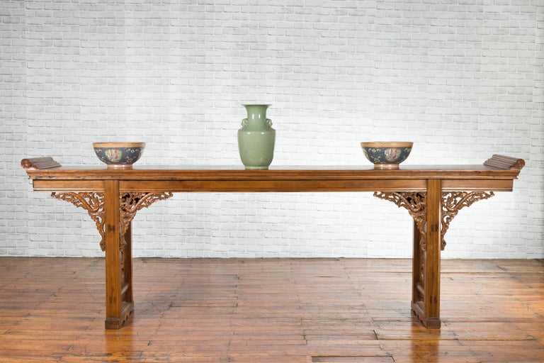 A Chinese early 20th century long elm altar console table from the Shandong province, with carved dragon motifs. Created in the Eastern province of Shandong during the early years of the 20th century, this long elm console table features a single