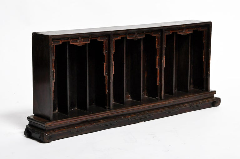 This slotted display shelf features narrow alcoves for holding ancestral figurines. It was probably part of a much more elaborate display built in tiers. The centerpiece of the display was an ancestral scroll painting. In front and below, a table