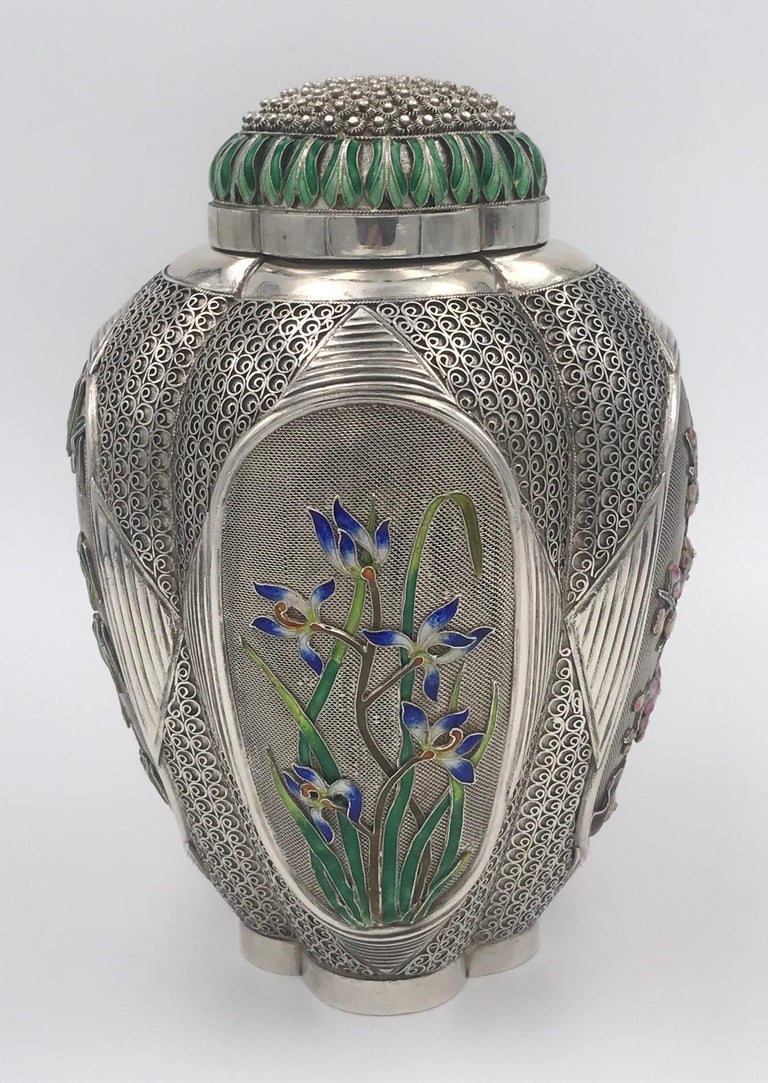 A beautifully decorated Chinese silver tea caddy with four enameled floral panels and further enamel to the pull-off lid.