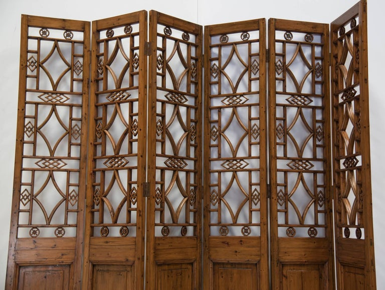 An early 20th century Chinese framed lattice-work six-panel screen with upper sections in openwork geometric motif. An exquisite design in pristine condition will work wonders for any large room of your home. Panels are easily arranged and hinges
