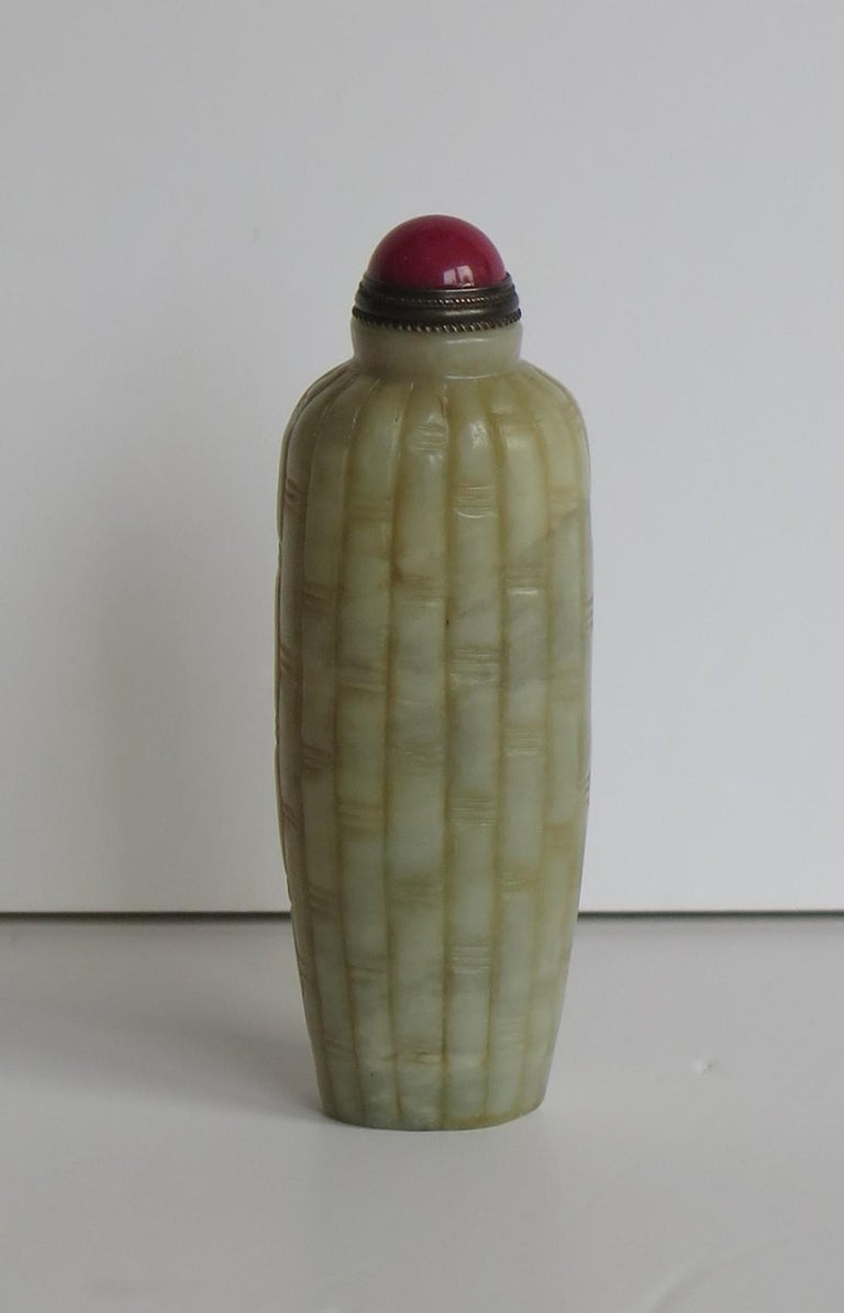 This is a beautiful Chinese snuff bottle, heavy for its size and hand carved from a mottled stone with a celadon color, which we attribute to Serpentine and dating to the early 20th century.  The bottle has a slightly tapering oval section and is