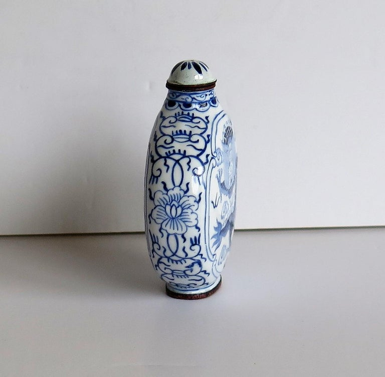 This is a Chinese enamelled snuff bottle, with a hand painted blue and white dragon on either side and a four character mark to the base, which we date to the 1940s.  The circular body of this bottle is made of copper or bronze. There is a hand