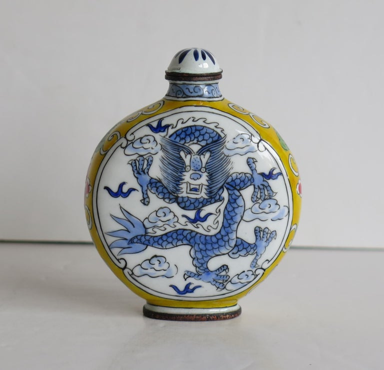 This is a Chinese enamelled snuff bottle, with a hand painted dragon on either side, with coloured side borders and a four character mark to the base, which we date to the 1940s.  The circular body of this bottle is made of copper or bronze. There