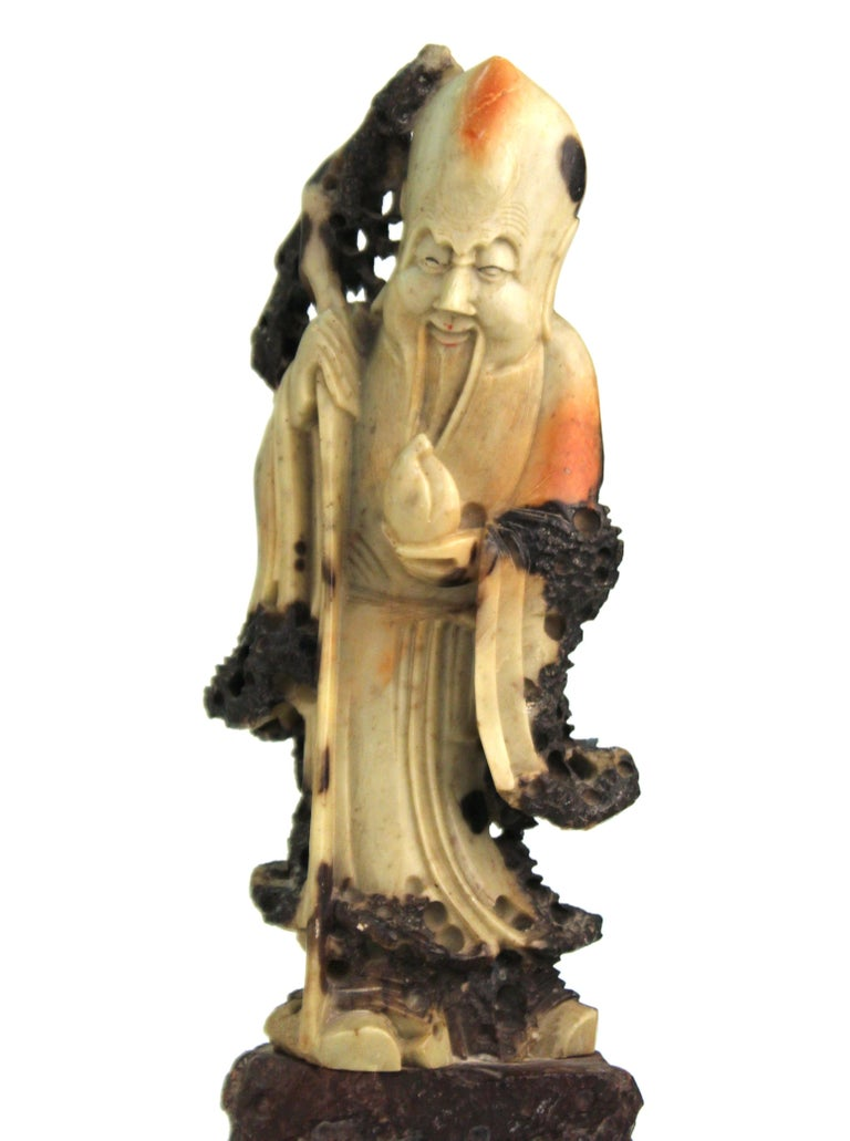 Chinese carving in soapstone depicting an old man holding a fruit and a cane atop a rock formation. The piece was carved in the mid-20th century and is in great vintage condition with age-appropriate wear to the bottom of the base.