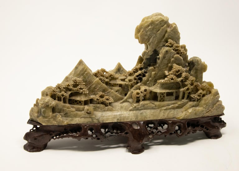 Offering this stunning soapstone carving of a Chinese landscape. The base is a carved piece of wood with openwork detail. The soapstone is mounted to the wood and starts at the base with two shelters, trees and rocks. In the background is mountains