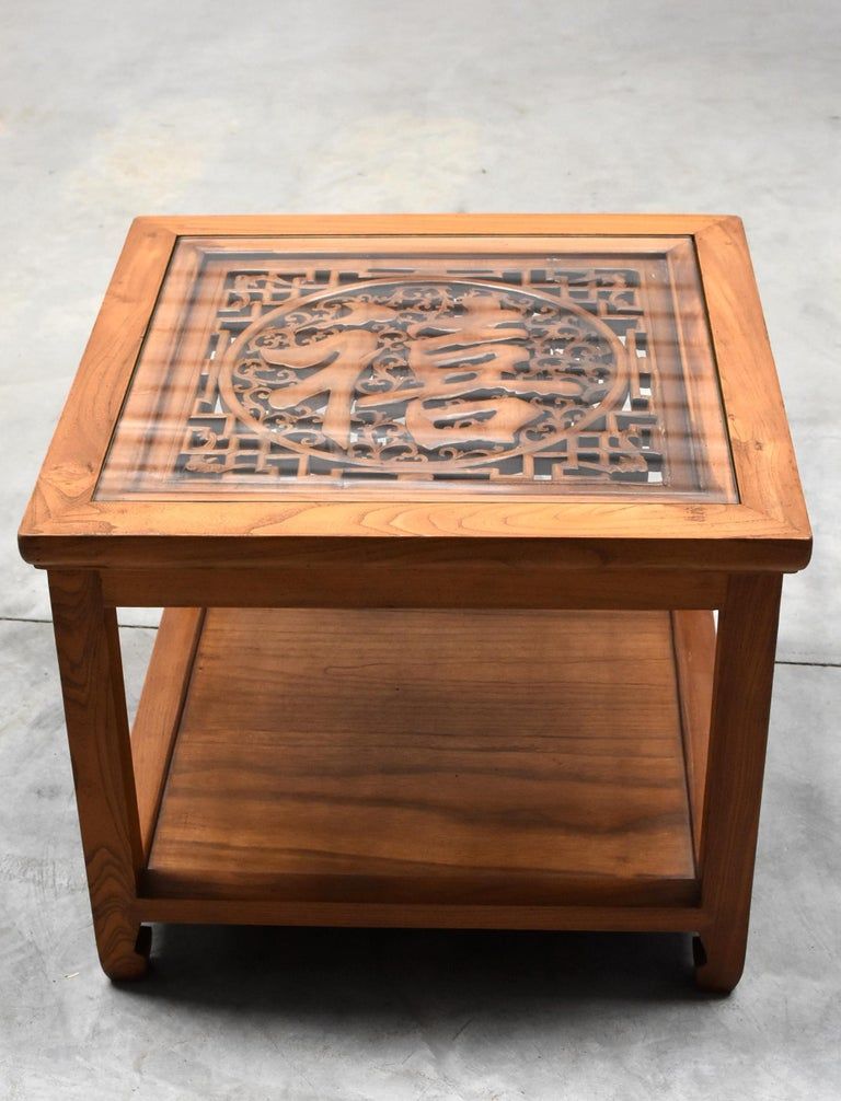 A beautiful natural finish square table made of solid elmwood. The tabletop is inset with a piece of hand-carved screen featuring the character