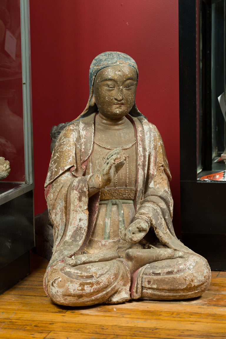 A Chinese Song Dynasty period painted stucco sculpture of Guanyin, Bodhisattva of Compassion, circa 960 to 1279. Created in China during the Song Dynasty, this seated sculpture depicts Guanyin the Bodhisattva of Compassion, wearing a dress, a coat