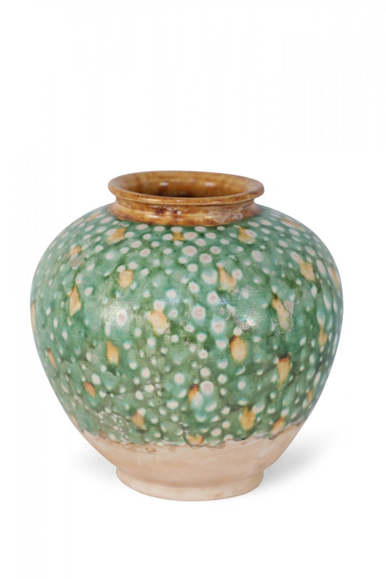 Antique Chinese Tang Dynasty-style vase crafted with the traditional tri-color glaze, or Sancai, utilizing brown, green and off-white, and with a glazed ochre-color opening.