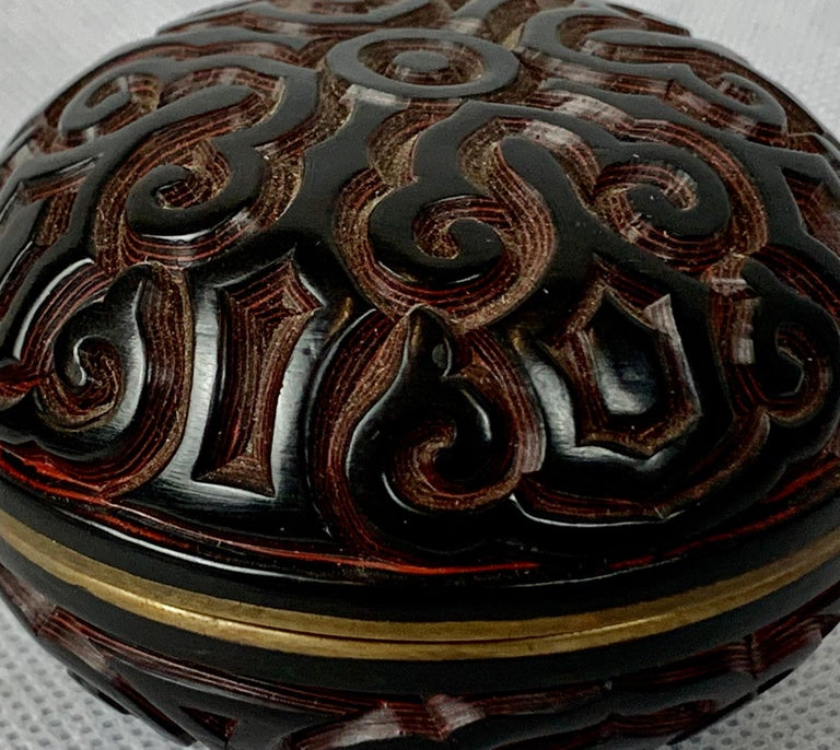 This is a Chinese two color Tixi cinnabar box or jar. Created early in the twentieth century with a stylized symbol design, black interior and brass collar. What makes this piece so interesting is the many layers of lacquer and very deep carving,