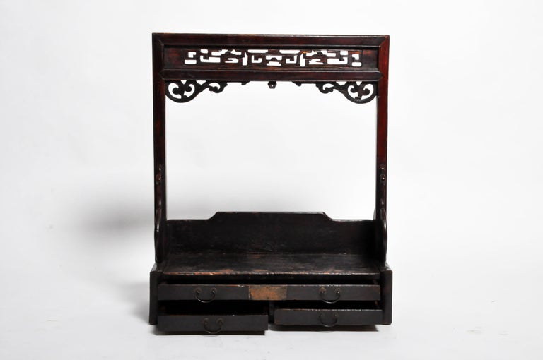 This lacquered wooden shelf probably held a mirror, jars of cosmetics, and articles of personal toilette. The piece has its original finish and the wood is in good condition. Origin: Shanghai, China, circa 1920.