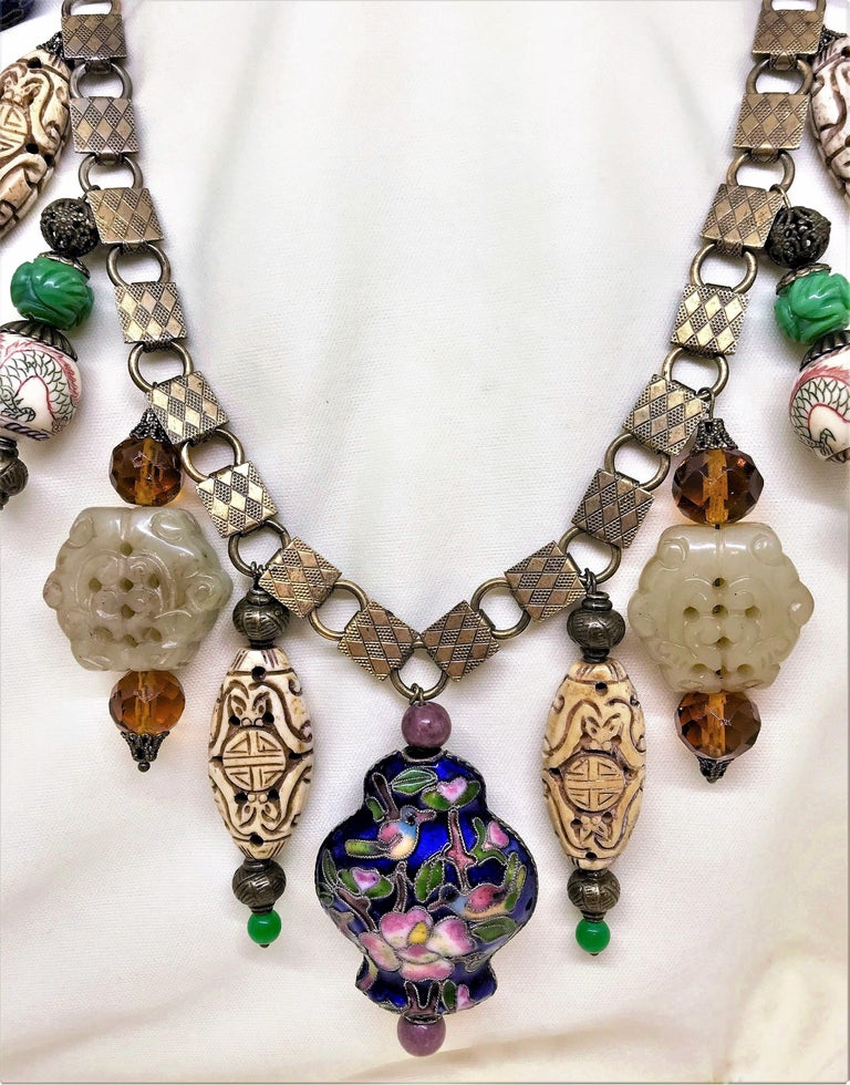 A newly created necklace from Little Treasures made from early 1900s ornate brass book-chain and a mix of contemporary and vintage Chinese beads of carved bone, porcelain dragons, cloisonné and carved Chinese Celadon beads. The necklace is