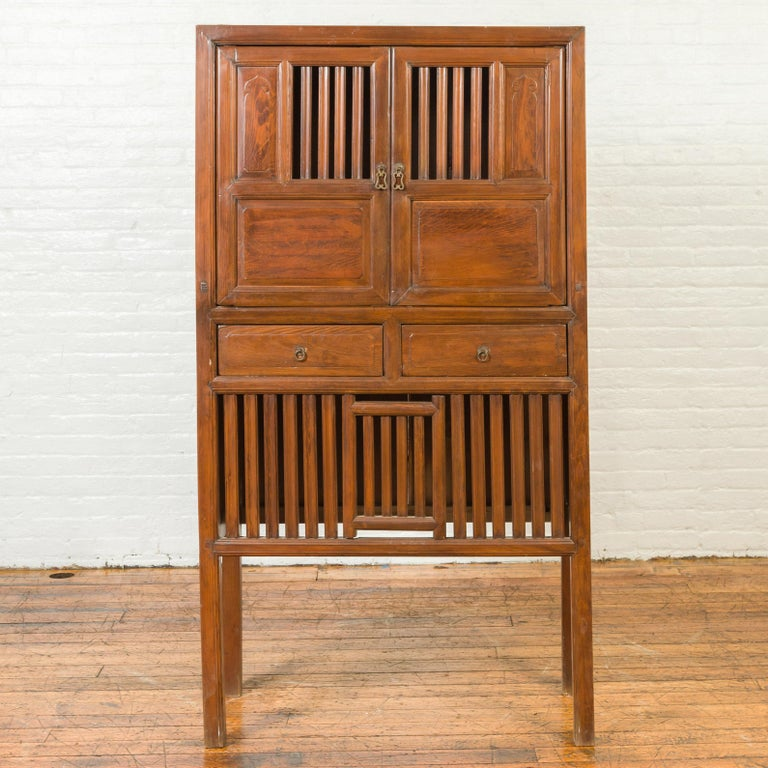 A Chinese vintage cabinet from the mid-20th century, with fretwork design, doors, drawers and tall legs. Created in China during the midcentury period, this wooden cabinet features a linear silhouette accented by perfectly organized fretwork