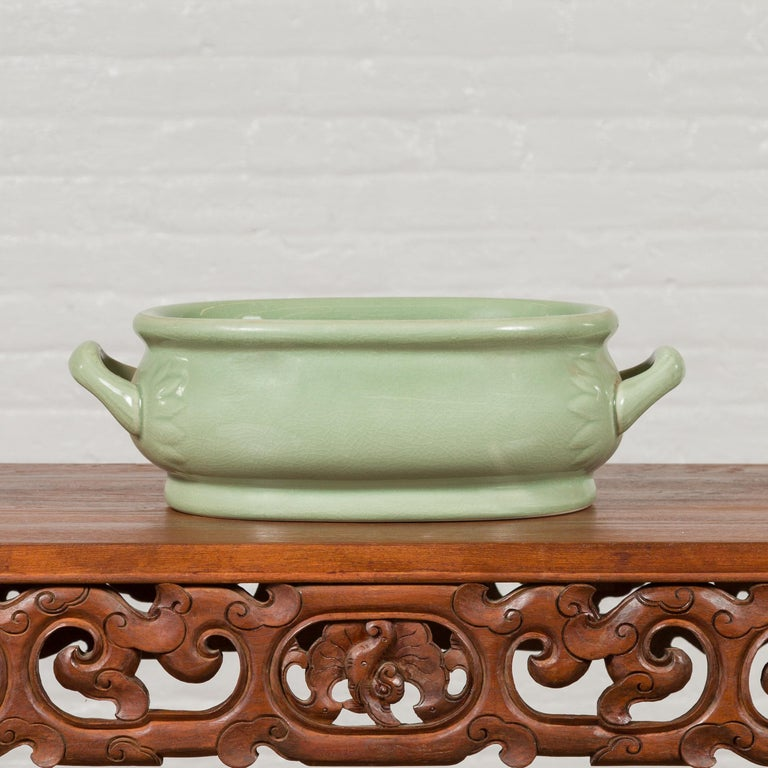 A Chinese vintage celadon foot bath from the mid-20th century, with two handles and foliage motifs. Created in China during the midcentury period, this celadon foot bath features an oval shape topped with a thick lip. The body, showcasing a slightly