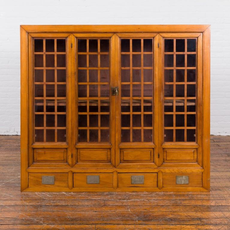 A Chinese vintage display cabinet from the mid 20th century, with glass doors and four drawers. Created in China during the midcentury period, this display cabinet features a linear silhouette perfectly complimented by a handsome honey brown patina.