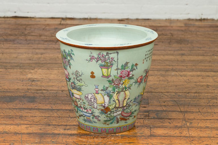 A Chinese vintage hand painted vase from the mid-20th century, with elephants, flowers, scholar's objects and fans. Created in China during the midcentury period, this large vase features a soft green ground adorned with a hand painted decor