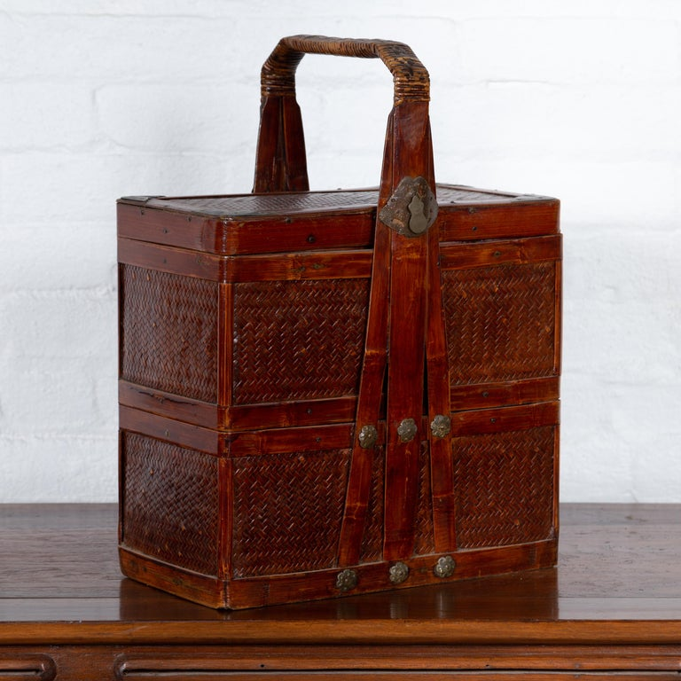 A Chinese vintage tiered rattan and lacquered wood picnic basket from the mid-20th century, with large handle and rich patina. Born in China during the midcentury period, this charming picnic basket features two independent sections, topped with a