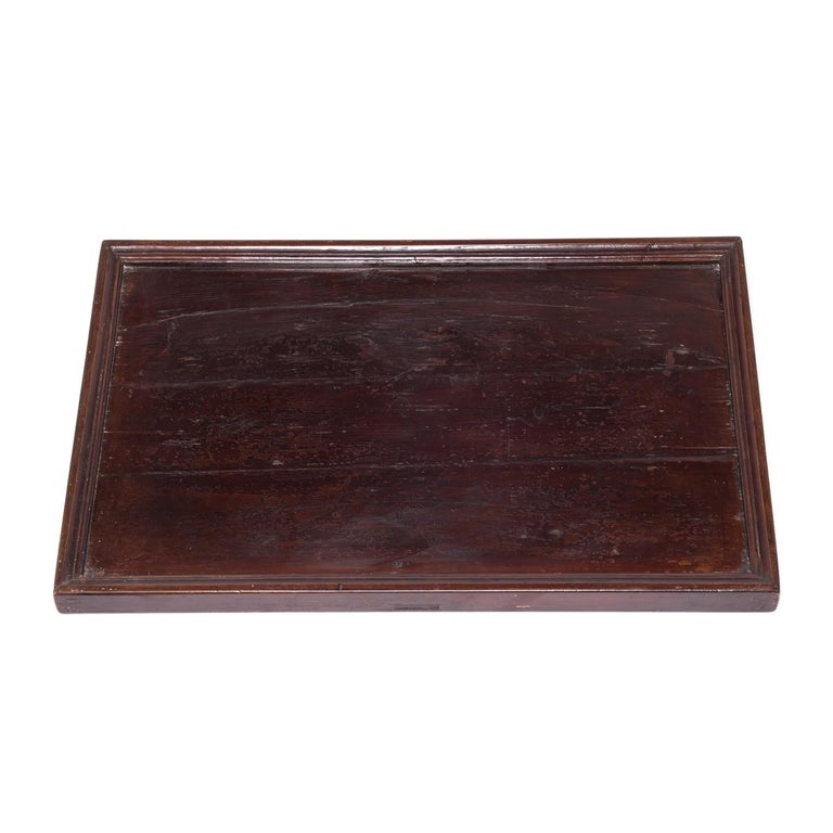 Simple lines, a modest form, and a layer of hand-brushed lacquer give this shallow Qing-dynasty footed tray a Provincial charm. A tray like this would have been used by a street vendor to display their wares to passersby. We love the simple tray as
