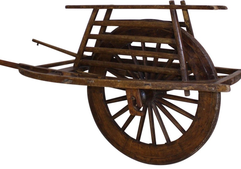 This wheelbarrow has a single, three-foot wheel with a carrying surface that encases the top of the wheel and is flanked by a platform on each side. The platform was designed for transporting supplies and people. The wheel's axle attaches to the