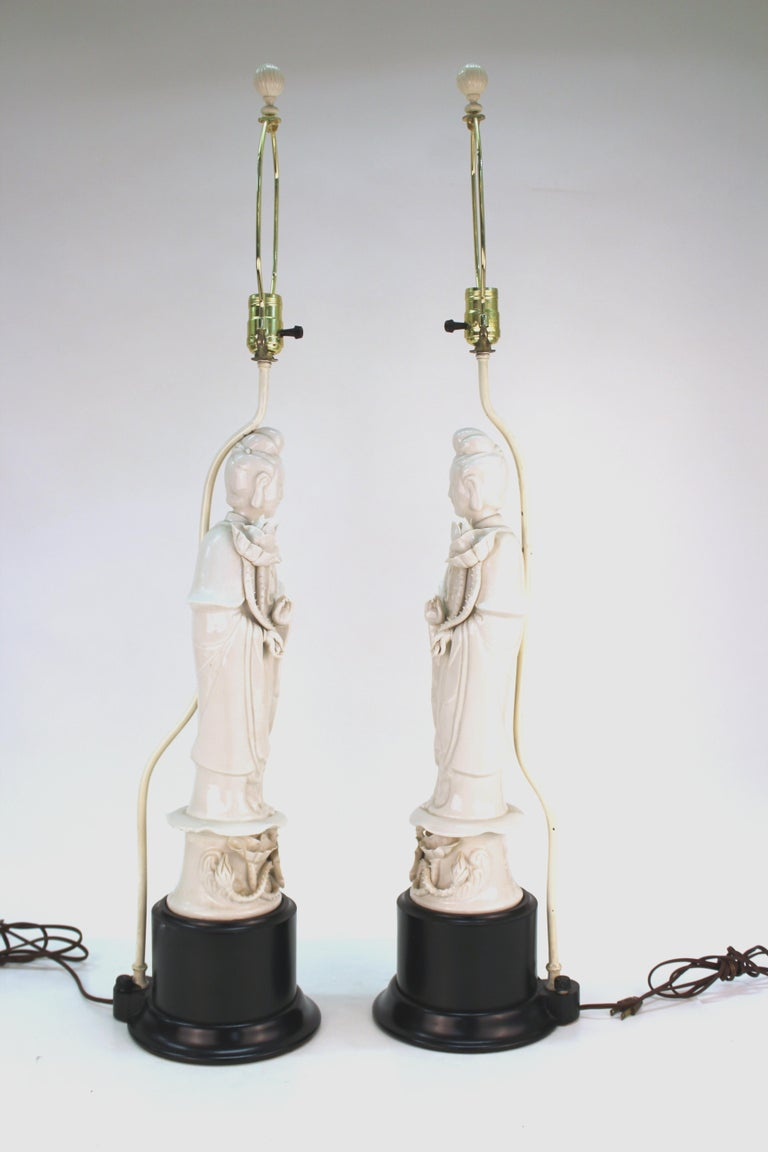 Pair of Chinese Export Guanyin Buddha table lamps in white ceramic atop black circular bases. The pair has Hong Kong marks on the back. There is some chipping to the finish on the metal pipes behind the Buddhas holding up the bulb sockets. In